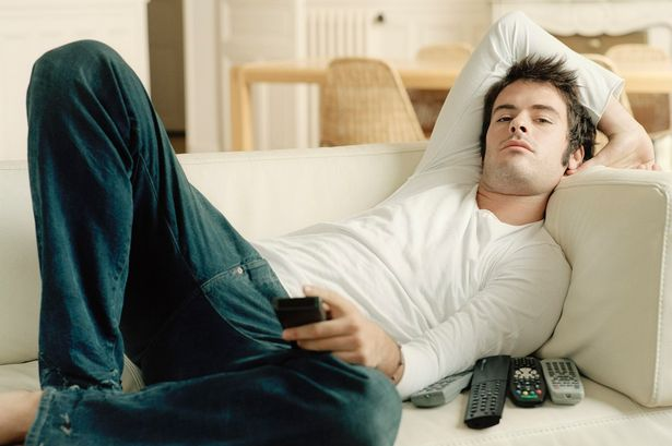 Man relaxing on sofa holding remote controls-189729