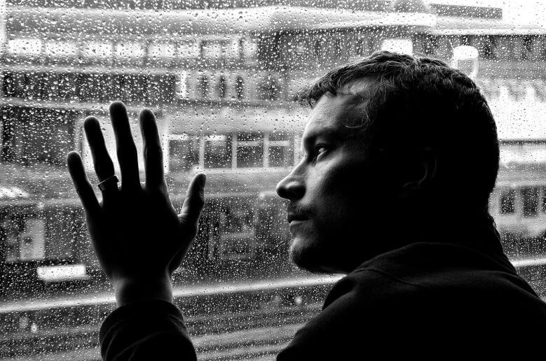 Depressed man by a window