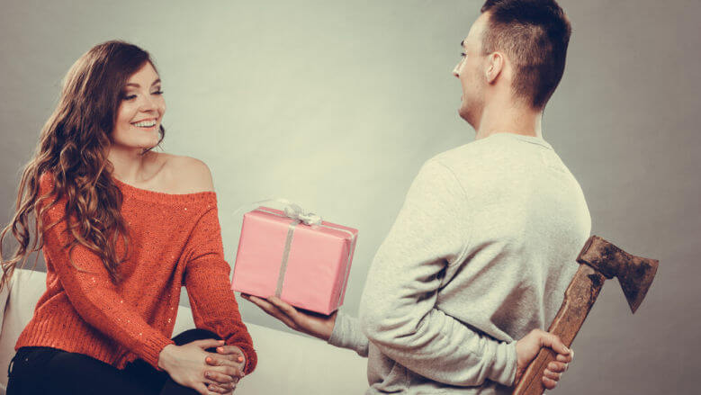 Sneaky insincere man holding axe giving gift present box to woman. Husband concealing hiding his true feelings from happy trusting wife. Untrue false intention.