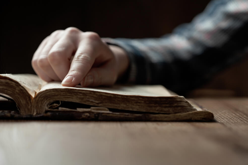 Woman finger presses on old bible book over wooden table and reading