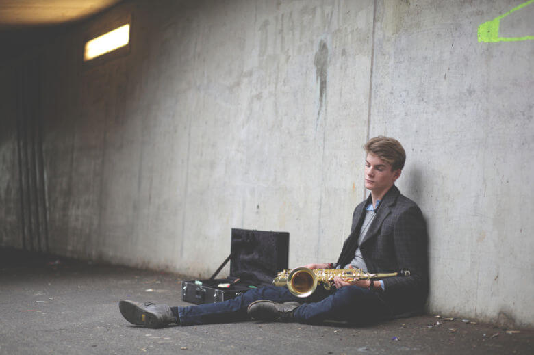 man sitting down with saxophone