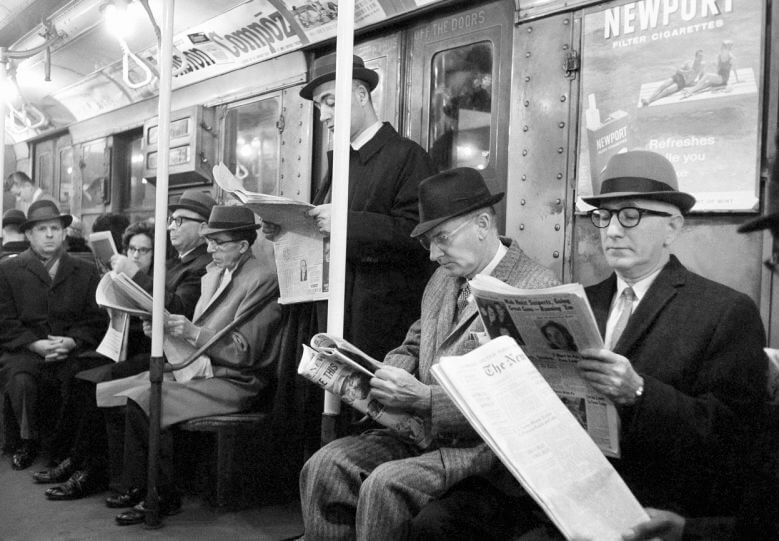 Reading the newspaper on a train