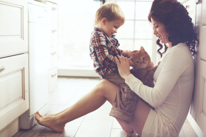 How to grow up and be more mature: Mother and child playing with cat
